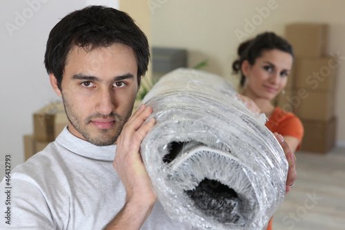 Couple carrying a rug