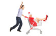 Happy guy pushing a shopping cart and female in christmas costum