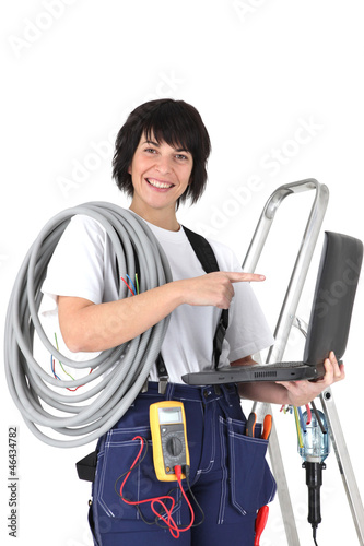 Female electrician with laptop and voltmeter