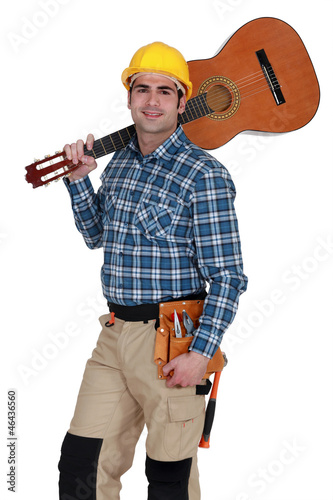 Builder carrying guitar over shoulder