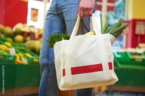 Mann trägt volle Einkaufstasche - 46436751