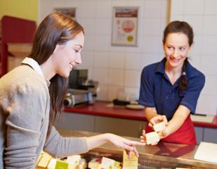Frau kauft Käse an der Käsetheke