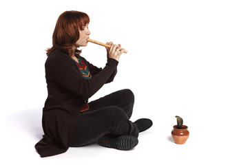 Redhead girl playing flute in front of snake