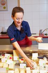 Mitarbeiterin bestückt Käsetheke