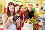 Frau sucht Geld an Supermarktkasse