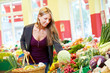 Frau kauft Kohl im Bioladen