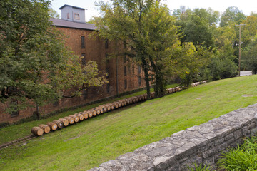 Line of whiskey barrels at distillery near warehouse