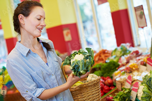 Frau kauft Blumenkohl im Bioladen