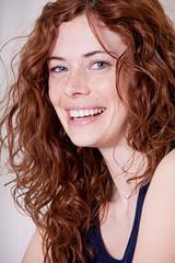 junge hübsche Frau mit Sommersprossen und lockigen harren lacht
