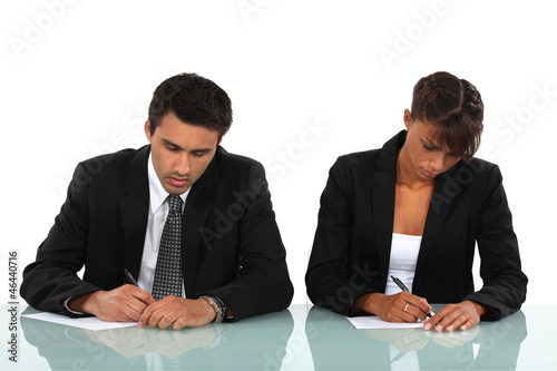 Two business people writing at a desk