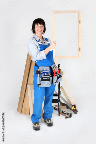 A carpenter holding up her handiwork