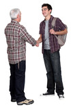 Younger and older men shaking hands