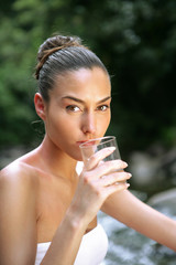 Woman drinking glass of water by stream