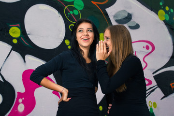 Two Friends Smiling and Gossiping Against a Graffiti Background