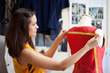 Fashion designer measuring a dress. Shallow depth of field.