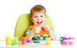 Happy little kid sitting at table and playing with colorful clay
