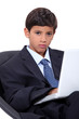 boy in an adult business suit with a laptop computer