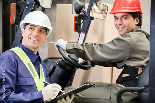 Portrait Of Forklift Driver With Supervisor Writing Notes