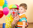 joyful kid with clown on birthday party