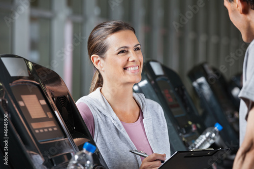 Instructor Looking At Male Client Exercising On Treadmill
