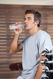 Man Drinking Water From Bottle At Health Club
