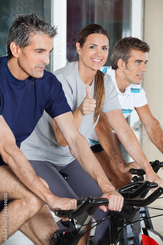 Woman Showing Thumbs Up Sign While Exercising With Friends On Sp