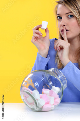 woman eating bonbons and making a silence sign