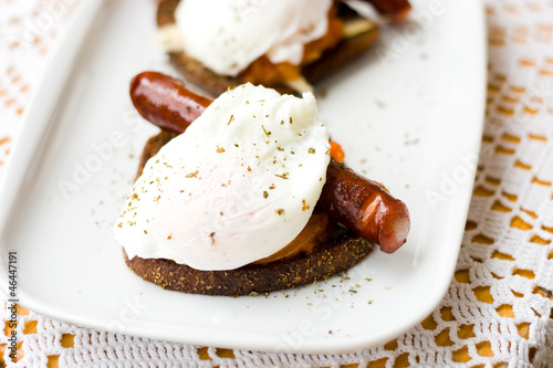 Poached egg with sausage on toast