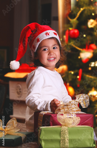 Sweet child smiles among Christmas gifts