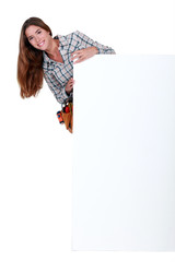 Happy female worker stood by blank advertising board