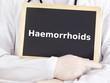 Doctor shows information on blackboard: haemorrhoids