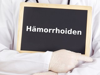 Doctor shows information on blackboard: hemorrhoids
