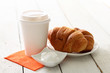 Coffee in plastic cup, sugar and croissants on a plate over wood