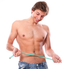 Sexy and handsome man measuring his belly after weight lose