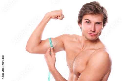 Naked torso man measuring his muscle over a white background