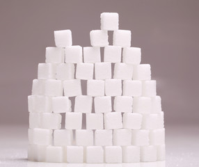Wall of white sugar cubes stacked up on grey background