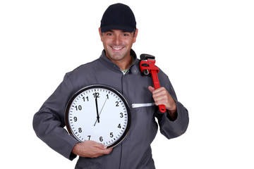 Handyman holding a pipe wrench and a clock