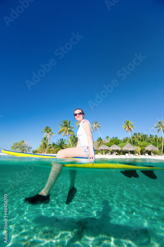 Woman sitting on a surfboard at ocean