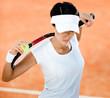 Woman in sports wear keeps tennis racket