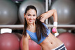 Young woman works out with dumbbells in gym