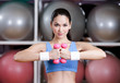 Young woman training her muscular system with dumbbells in gym