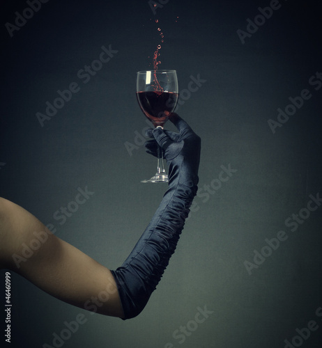 Woman's hand in glove with a glass of red wine.