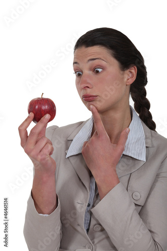 A business woman looking weirdly at an apple.