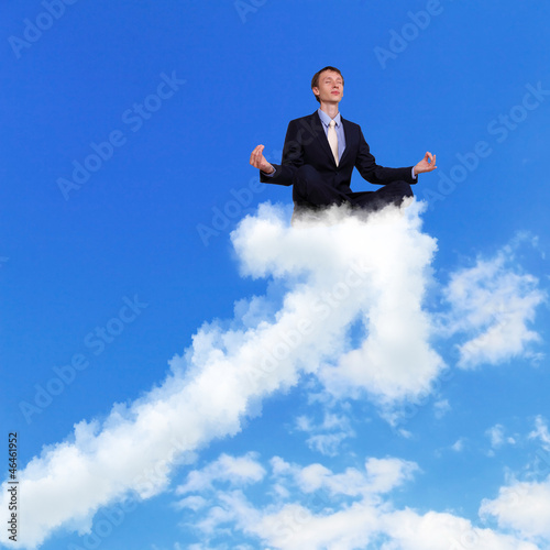 Businessman meditating sitting on the cloud