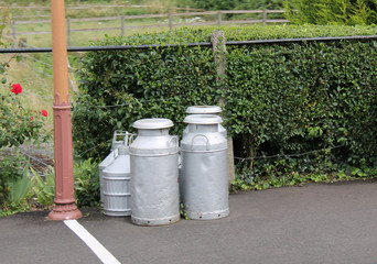 Some Milk Churns Standing on a Railway Platform.