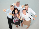 Successful young business people showing thumbs up sign