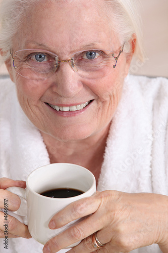 Portrait of an elderly woman drinking coffee