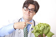 Young attractive man doctor with green salad