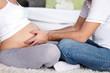 man touching stomach his pregnant woman