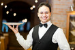 Professional waiter holding an empty dish